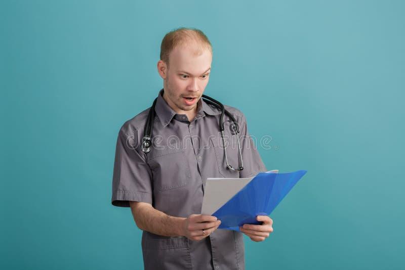 Os jovens surpreenderam o doutor masculino que guarda um dobrador com papéis no fundo azul fotografia de stock