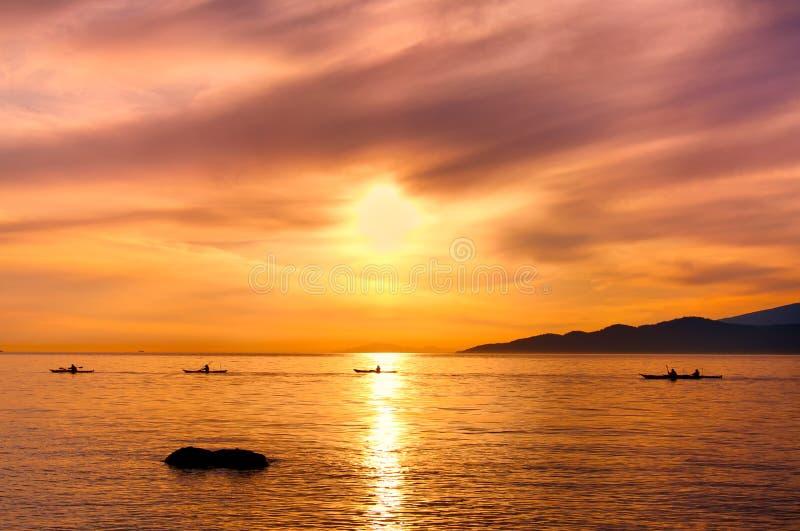 Os Kayakers mostram em silhueta no oceano durante o por do sol alaranjado fotos de stock