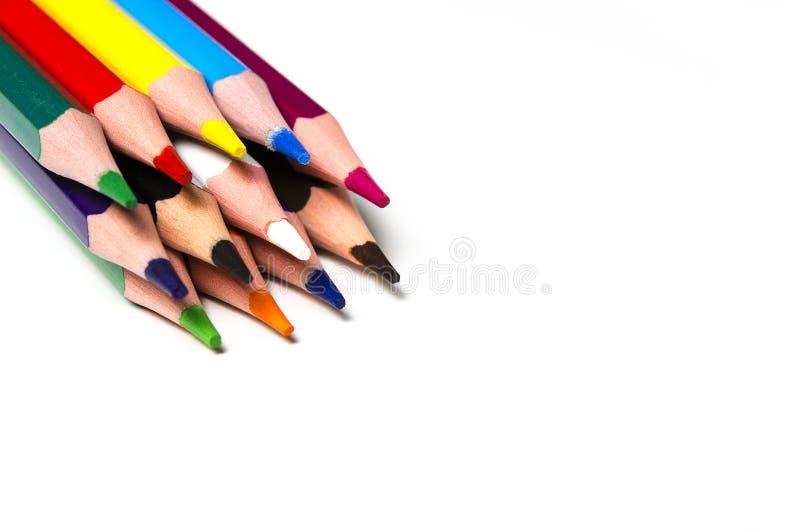 Os lápis afiados coloridos encontram-se em um fundo branco fotografia de stock