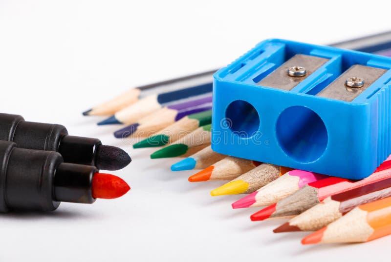 Os lápis coloridos e corrigem o apontador no fundo branco fotografia de stock royalty free