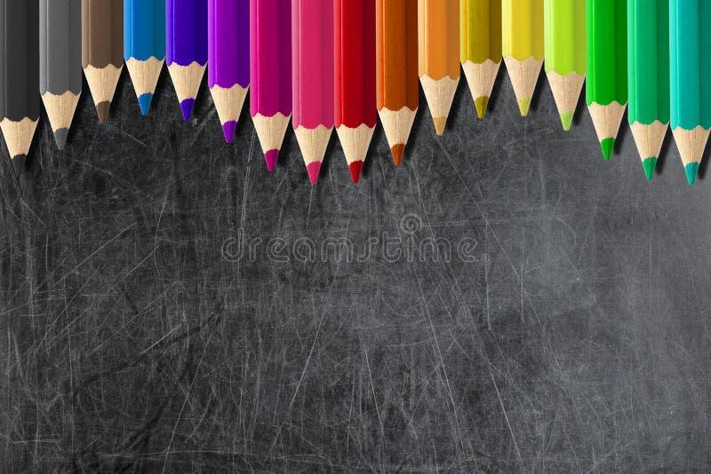 Os lápis coloridos que formam a onda limitam o quadro-negro ou o chalkbo vazio fotos de stock