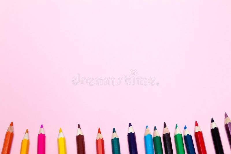 Os lápis coloridos sem emenda do arco-íris enfileiram com a onda em um mais baixo lado, diversos arranjos, no papel cor-de-rosa C foto de stock