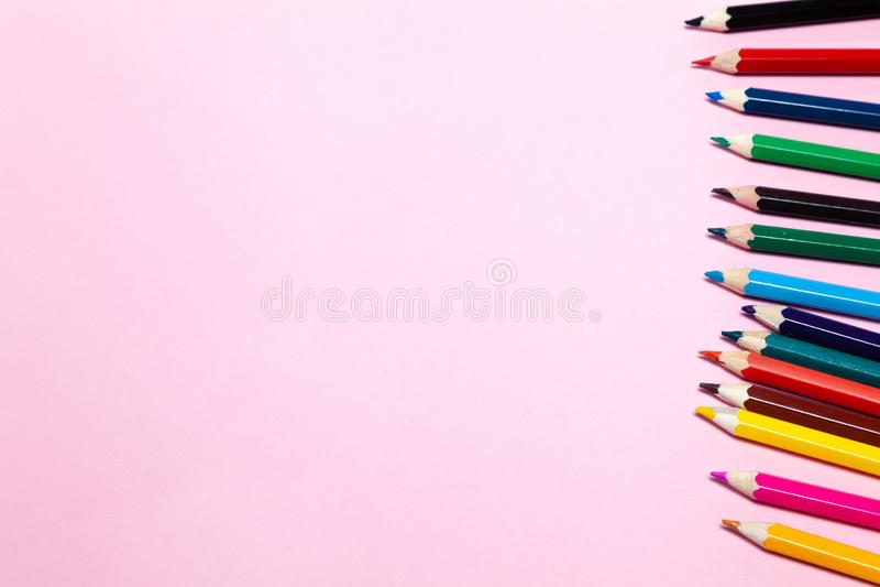 Os lápis coloridos sem emenda do arco-íris enfileiram com a onda em um mais baixo lado, diversos arranjos, no papel cor-de-rosa C imagem de stock