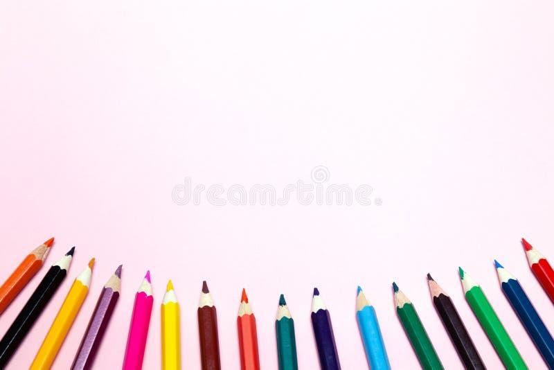 Os lápis coloridos sem emenda do arco-íris enfileiram com a onda em um mais baixo lado, diversos arranjos, no papel cor-de-rosa C fotos de stock royalty free