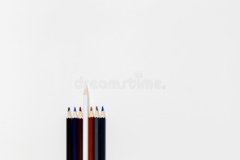 Os lápis escuros e um destacaram o lápis branco no fundo branco imagens de stock royalty free