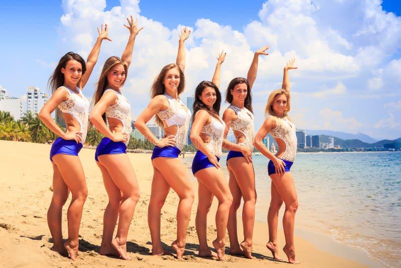 Os líder da claque levantam na linha mãos para cima na praia contra o mar fotografia de stock