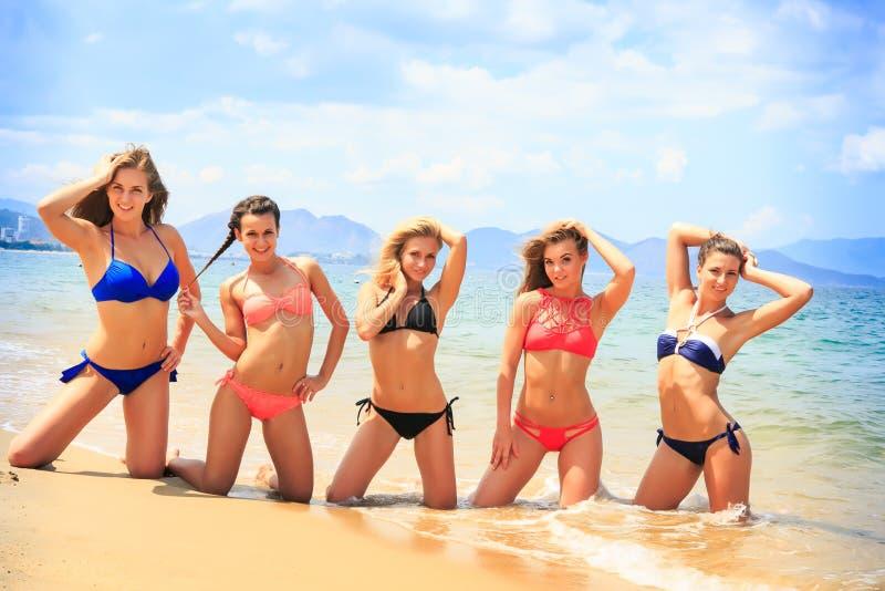 Os líder da claque levantam na linha mãos para cima na praia contra o mar fotos de stock