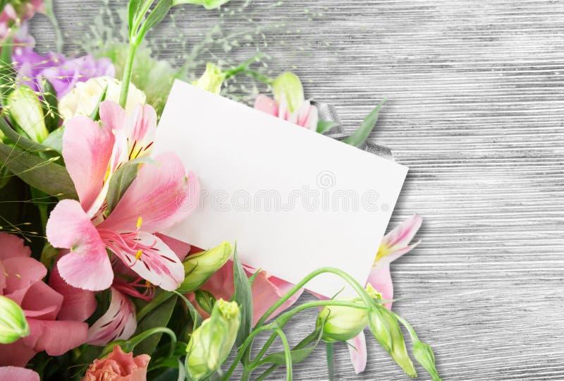 Os lírios bonitos florescem o ramalhete e o cartão vazio sobre foto de stock