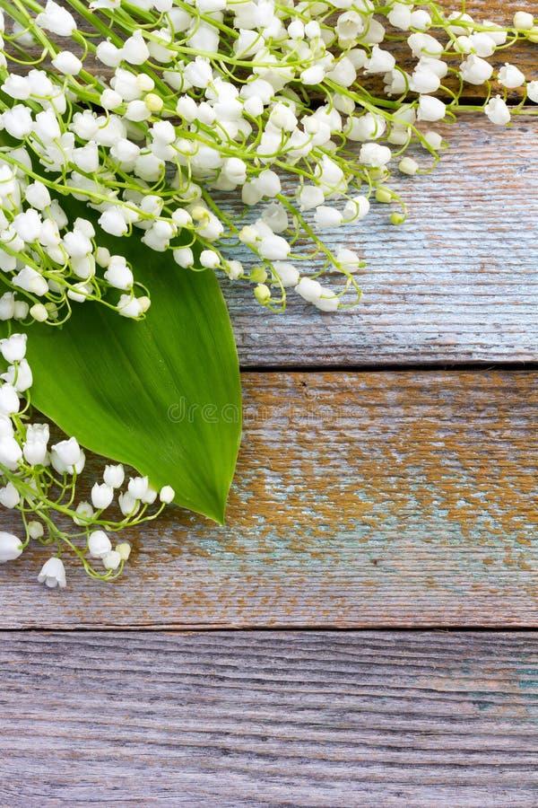 Os lírios de flores brancas do vale dispersaram no fundo de madeira velho fotos de stock royalty free