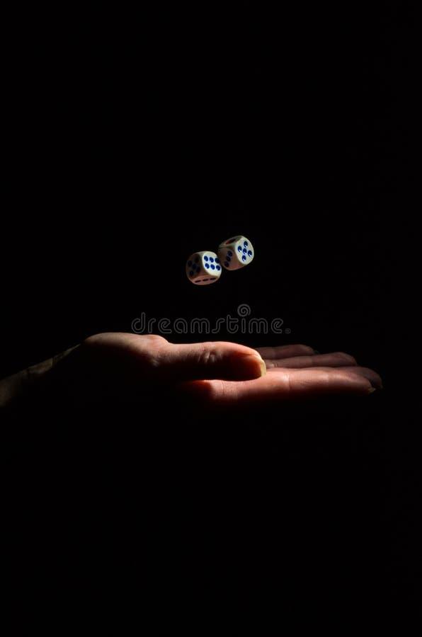 Os lances da mão cortam para jogar um jogo de mesa em um fundo preto imagens de stock