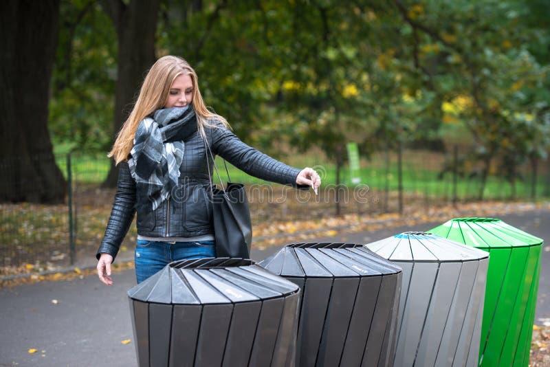 Os lances da mulher reciclam o lixo de papel no lixo que classifica o desperdício imagem de stock