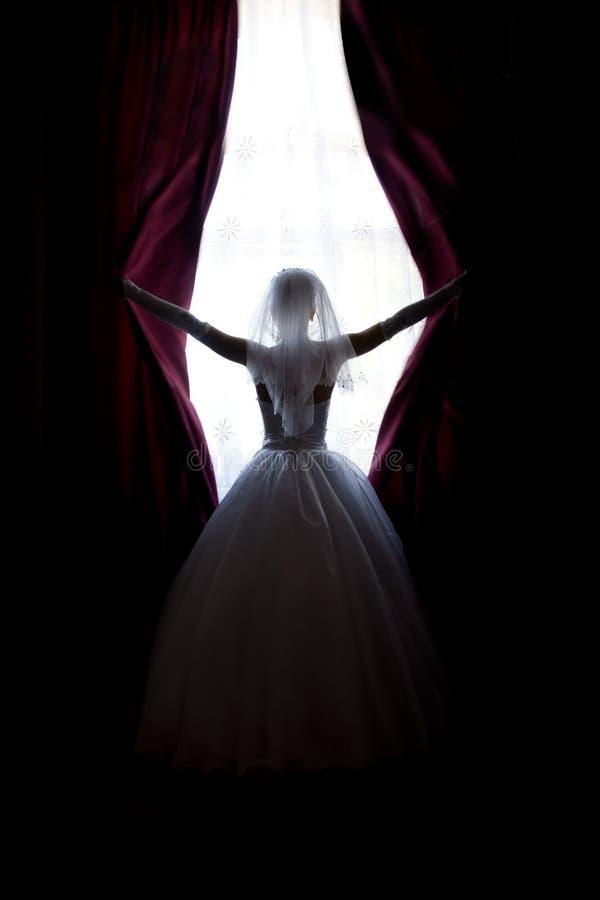 Os lances da noiva abrem cortinas na janela fotografia de stock