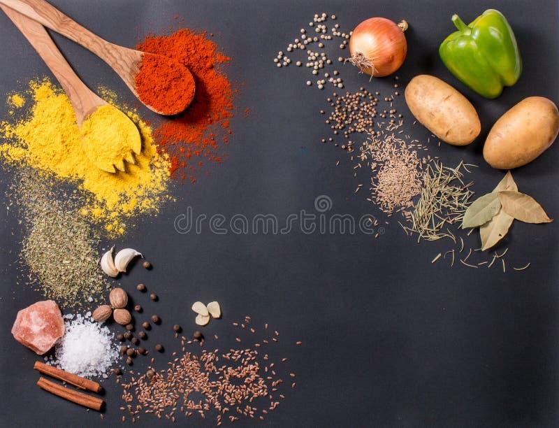 Os legumes frescos, as especiarias e as ervas dispersaram no fundo escuro Ingredientes naturais e bio para cozinhar o espaço da c fotografia de stock royalty free