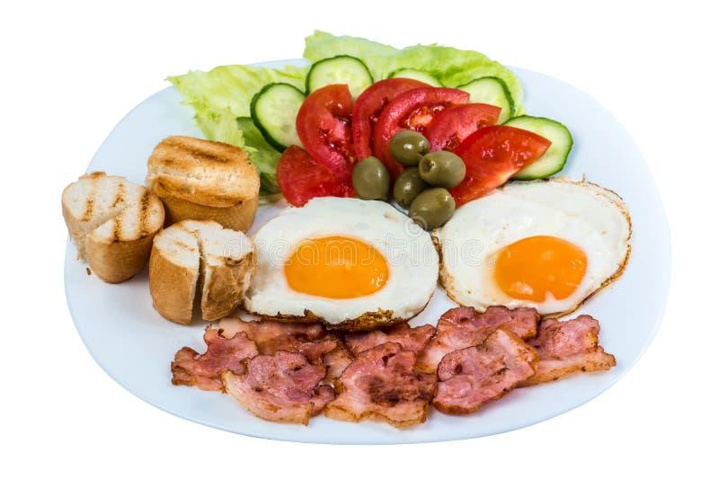 Os legumes frescos do ovo frito do café da manhã fritaram o bacon e as azeitonas em uma placa branca foto de stock royalty free