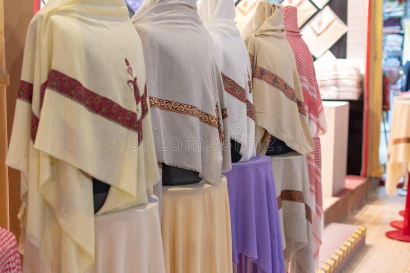 Os lenços principais do dishdash masculino branco colorido alinham para a venda dentro no mercado da aldeia global em Dubai, Emir imagens de stock