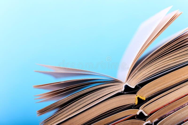 Os livros abertos são empilhados na mesa, em um fundo azul Trabalhos de casa difíceis na escola, uma montanha do conhecimento imagens de stock royalty free