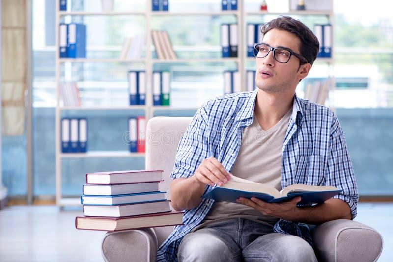 Os livros de leitura do estudante e preparação para exames na biblioteca fotografia de stock
