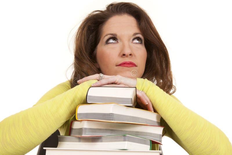 Os livros do daydream da mulher olham acima foto de stock