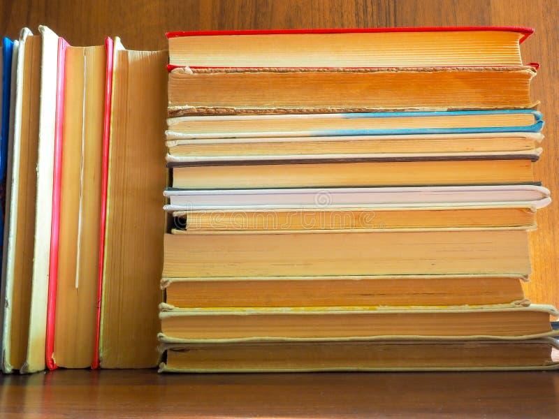 Os livros e os livros de texto lidos e bloqueados estão esperando o começo do ano escolar e seus leitores e estudantes foto de stock