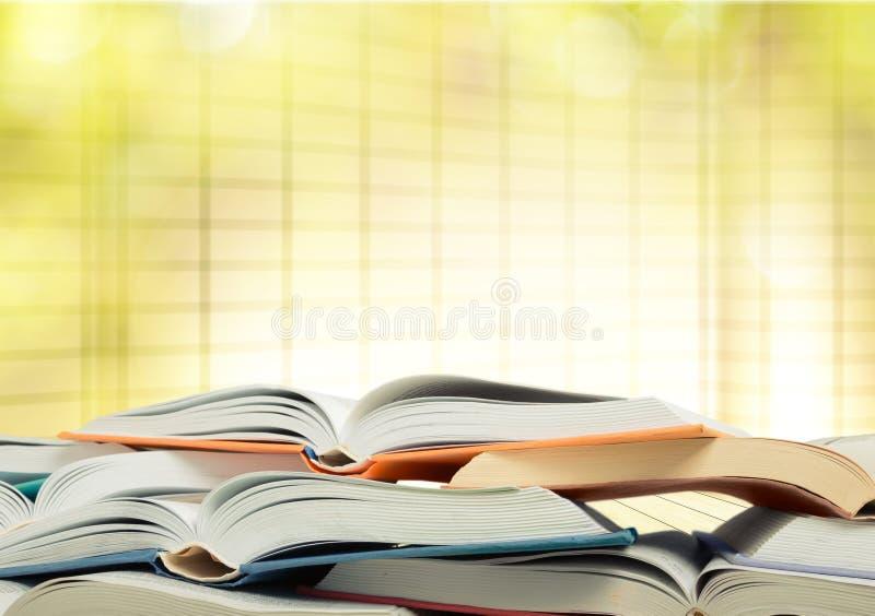 Os livros são abertos e empilhados junto na luz imagens de stock