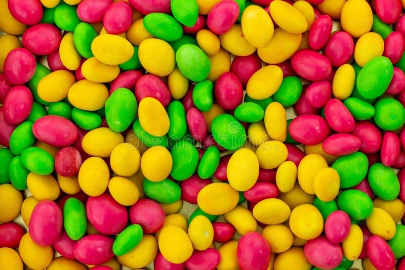 Os lotes coloridos brilhantes do fundo de drageias multi-coloridas amarelas verdes do rosa dos doces baseiam o projeto festivo fotografia de stock