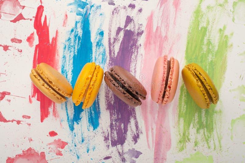 Os lotes dos macarons coloriram em um fundo brilhante da aquarela da cor Conceito da arte dos confeitos Cookies megaltic delicios foto de stock royalty free