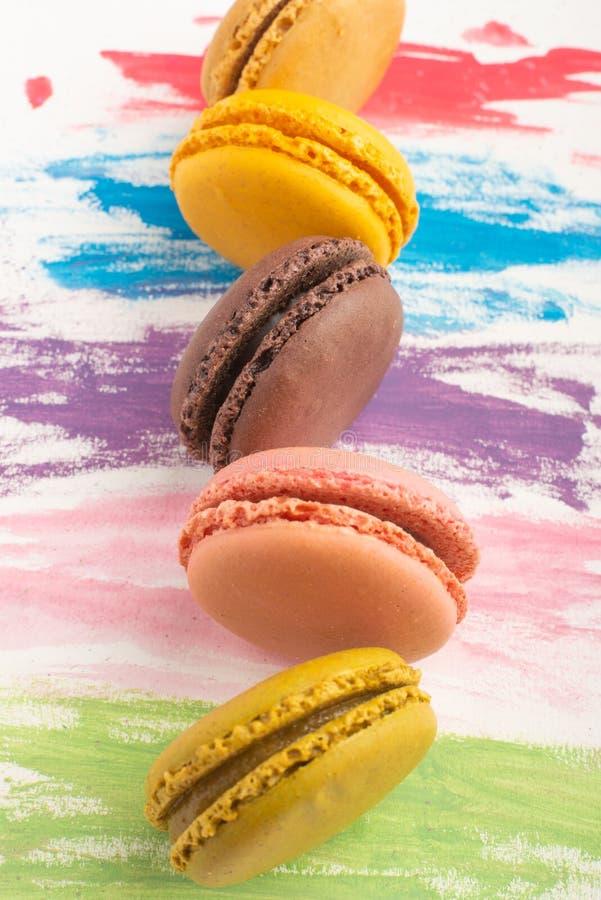 Os lotes dos macarons coloriram em um fundo brilhante da aquarela da cor Conceito da arte dos confeitos Cookies megaltic delicios fotos de stock royalty free