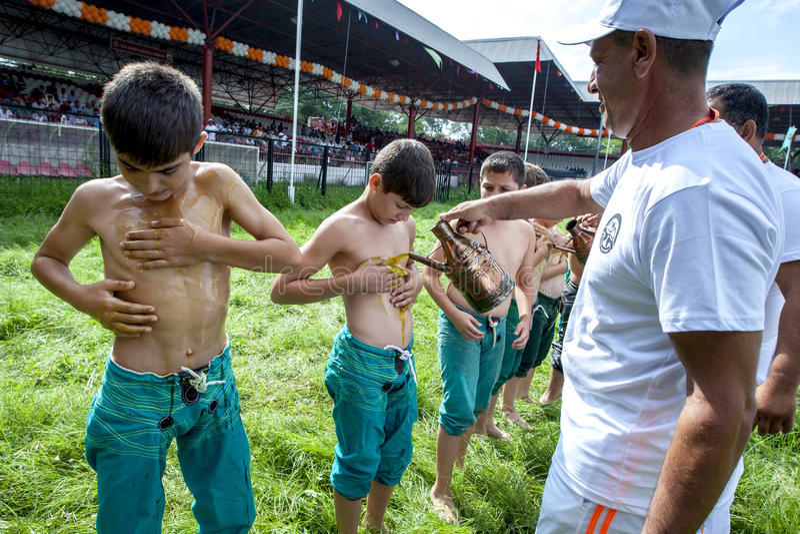 Os lutadores novos têm o azeite derramado em seus corpos antes do começo da competição no Fest turco da luta romana do óleo de Ki fotografia de stock