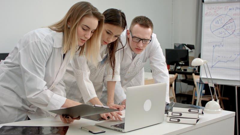 Os médicos team usando o portátil no escritório fotos de stock