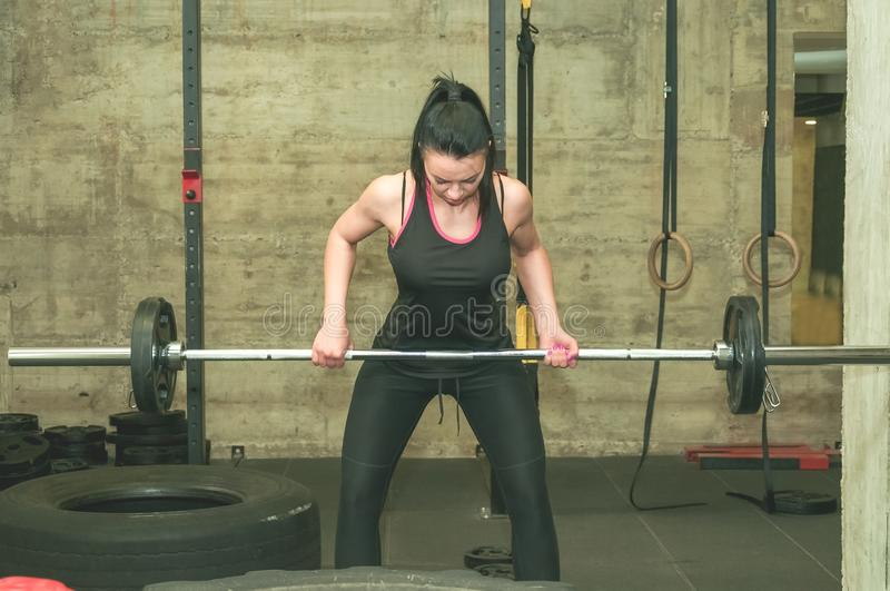 Os músculos traseiros novos da menina bonita e atrativa worm acima do exercício com peso claro no gym, pessoa real do barbell que foto de stock royalty free