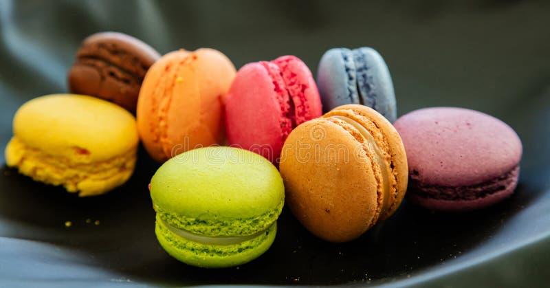 Os macarons coloridos no fundo preto, fecham-se acima da vista fotos de stock royalty free