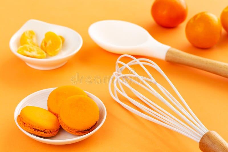 Os macarons ou os bolinhos de amêndoa alaranjados em uns pires brancos com tangerina descascaram segmentos, o batedor de ovos bra fotografia de stock