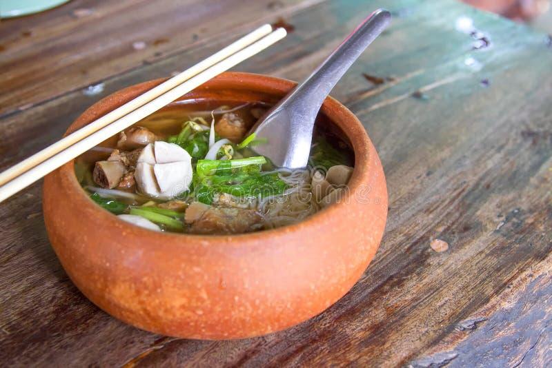 Os macarronetes de arroz do potenciômetro de argila puseram sobre uma tabela de madeira fotos de stock royalty free