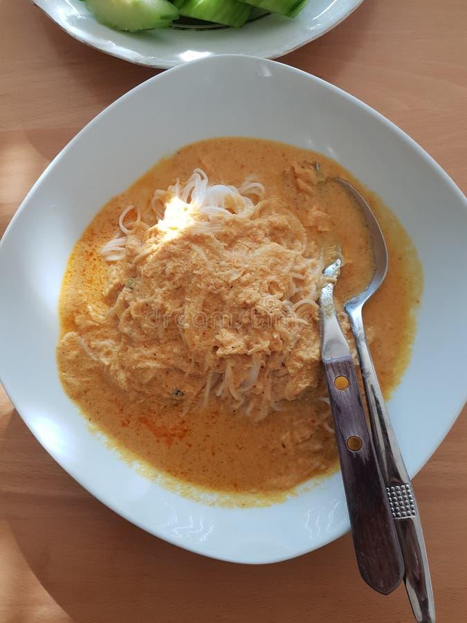 Os macarronetes de arroz tailandeses, macarronetes frescos com caril tailandês picante são um alimento local em do sul de Tailând fotografia de stock