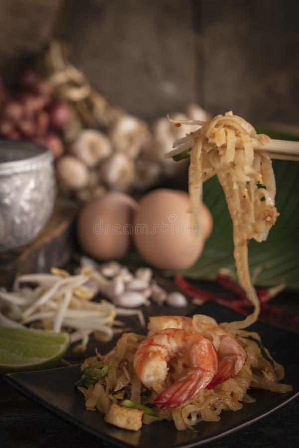 Os macarronetes ou os tailandeses fritados tailandeses da almofada com camarão na placa preta colocada na tabela de madeira lá sã fotos de stock royalty free