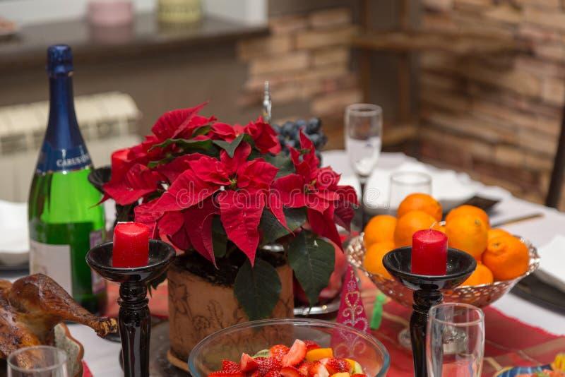 Os mandarino, champanhe, velas e poinsétia imagens de stock