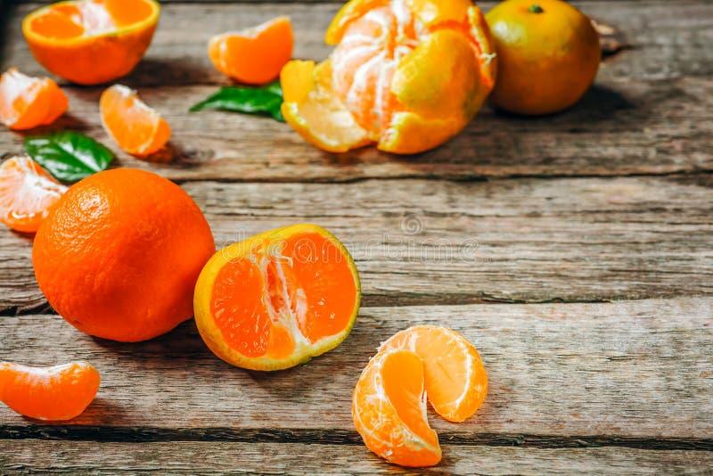 Os mandarino das tangerinas, clementina, citrinas com as folhas sobre o fundo de madeira rústico com espaço da cópia imagens de stock