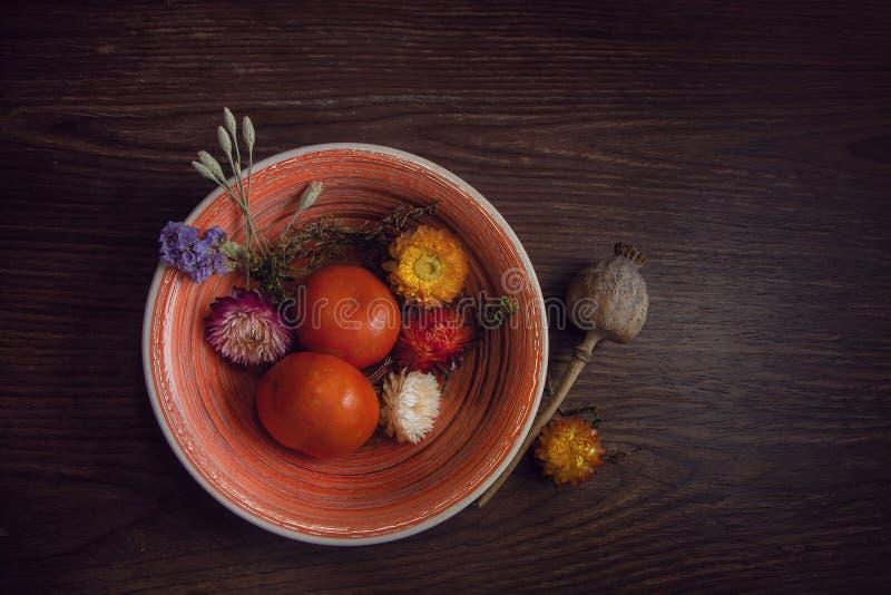 Os mandarino e as flores encontram-se em uma bacia em uma tabela marrom de madeira em seguida imagem de stock royalty free
