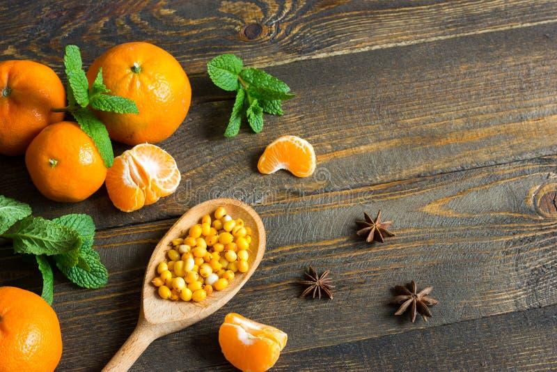 Os mandarino nas placas com hortelã, espinheiro cerval de mar e anis de estrela fotos de stock