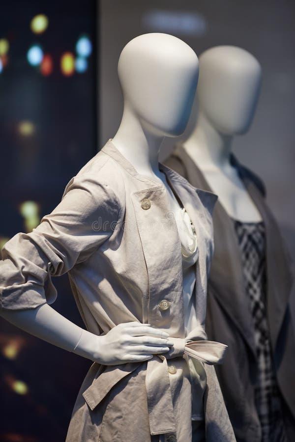 Os manequins que estão na exposição da janela de loja da roupa ocasional das mulheres compram fotografia de stock royalty free