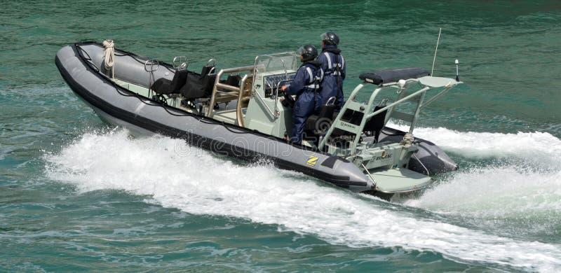 Os marinheiros reais da marinha de Nova Zelândia montam um inflat Rígido-hulled Zodiak fotografia de stock