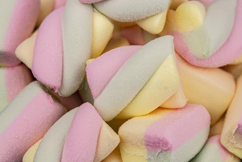 Os marshmallows coloridos rolam na forma de um espiral, fundo do close-up Sobremesa verde azul do marshmallow do rosa amarelo doc imagens de stock royalty free