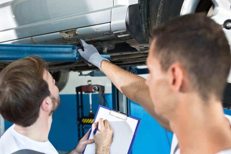 Os mecânicos mostram onde o defeito no carro imagens de stock
