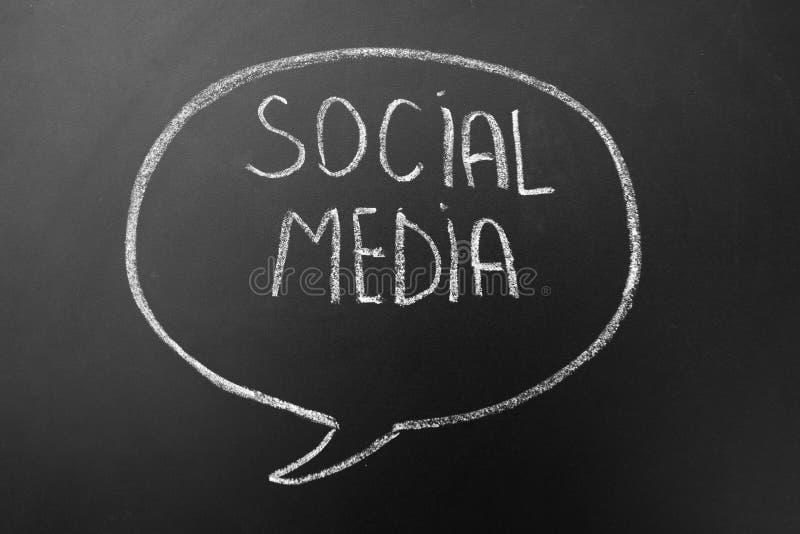 Os meios sociais - conceito dos trabalhos em rede do Internet - text escrito à mão com giz branco em um quadro-negro no discurso, fotografia de stock royalty free