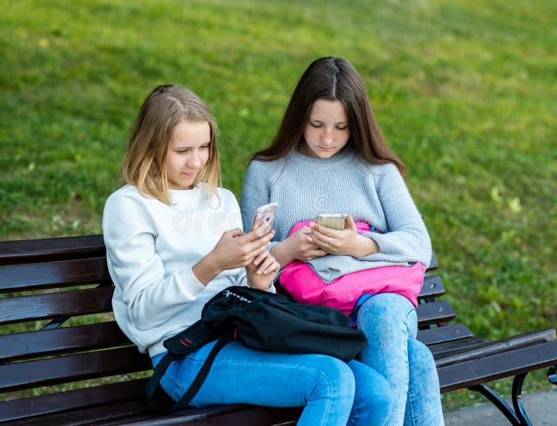 Os melhores amigos no verão no ar fresco do parque A estudante das meninas em um banco guarda telefones espertos É correspondido  fotografia de stock