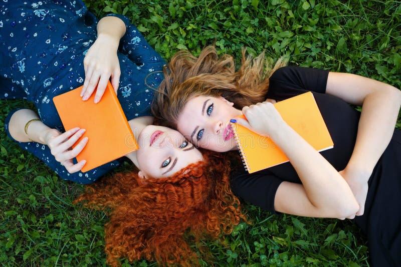 Os melhores amigos são estudantes no gramado imagens de stock royalty free