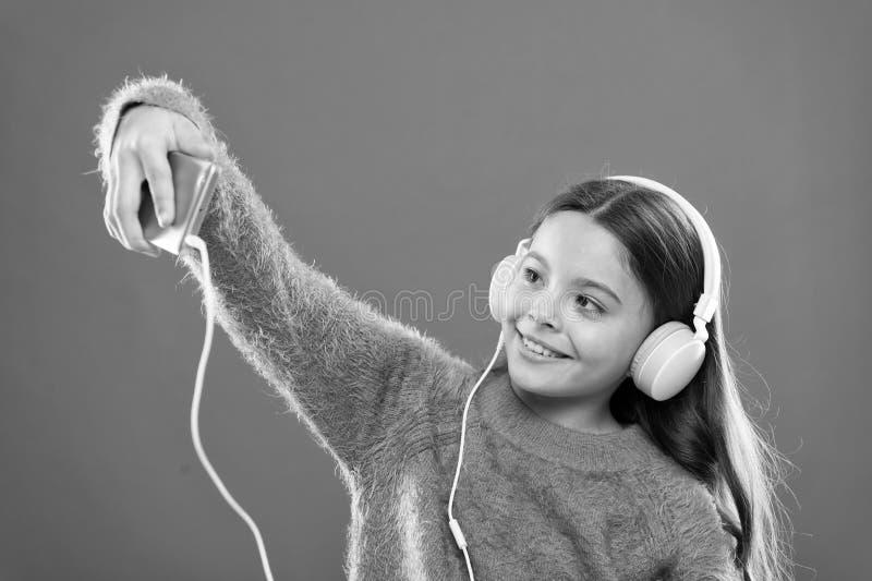 Os melhores apps da m?sica para livre Aprecie o conceito da m?sica Aprecie o som perfeito A crian?a da menina escuta fones de ouv imagem de stock royalty free