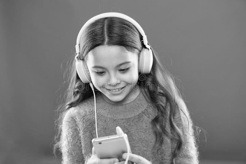 Os melhores apps da m?sica para livre Aprecie o som perfeito A crian?a da menina escuta fones de ouvido e smartphone modernos da  fotografia de stock