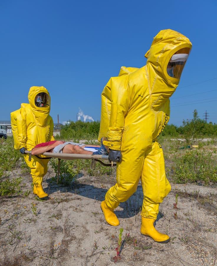 Os membros da equipa de Hazmat têm vestido ternos protetores para protegê-los dos materiais perigosos fotos de stock