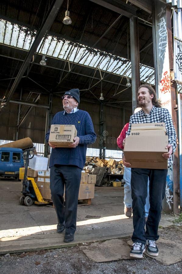 Os membros e os voluntários de BookCycle Reino Unido levam caixas dos livros imagens de stock royalty free
